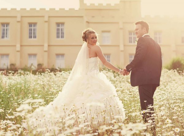 Newly weds walking in a wild flower garden, Pentillie Castle in the background