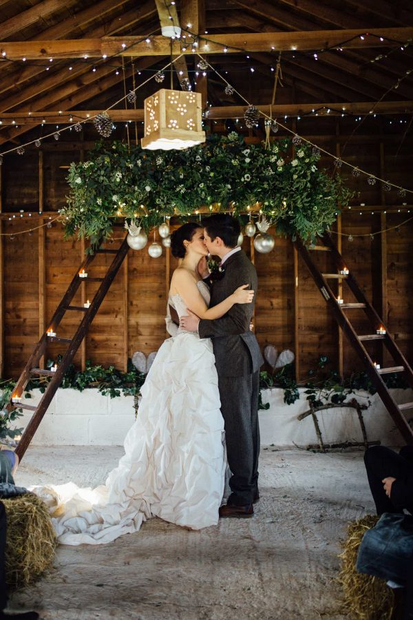 A photograph of newly wed kissing in a barn. The wedding theme rustic opulence