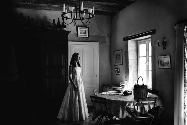Bride staring out a window in a beautiful wedding dress by Debs Ivelja Photography