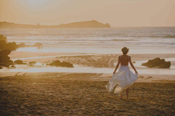 A photograph of a bride walking along a beautiful sandy beach at sunset a beautifully stylish beach wedding