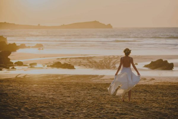 A photograph of a bride walking along a beautiful sandy beach at sunset a beautifully stylish beach wedding