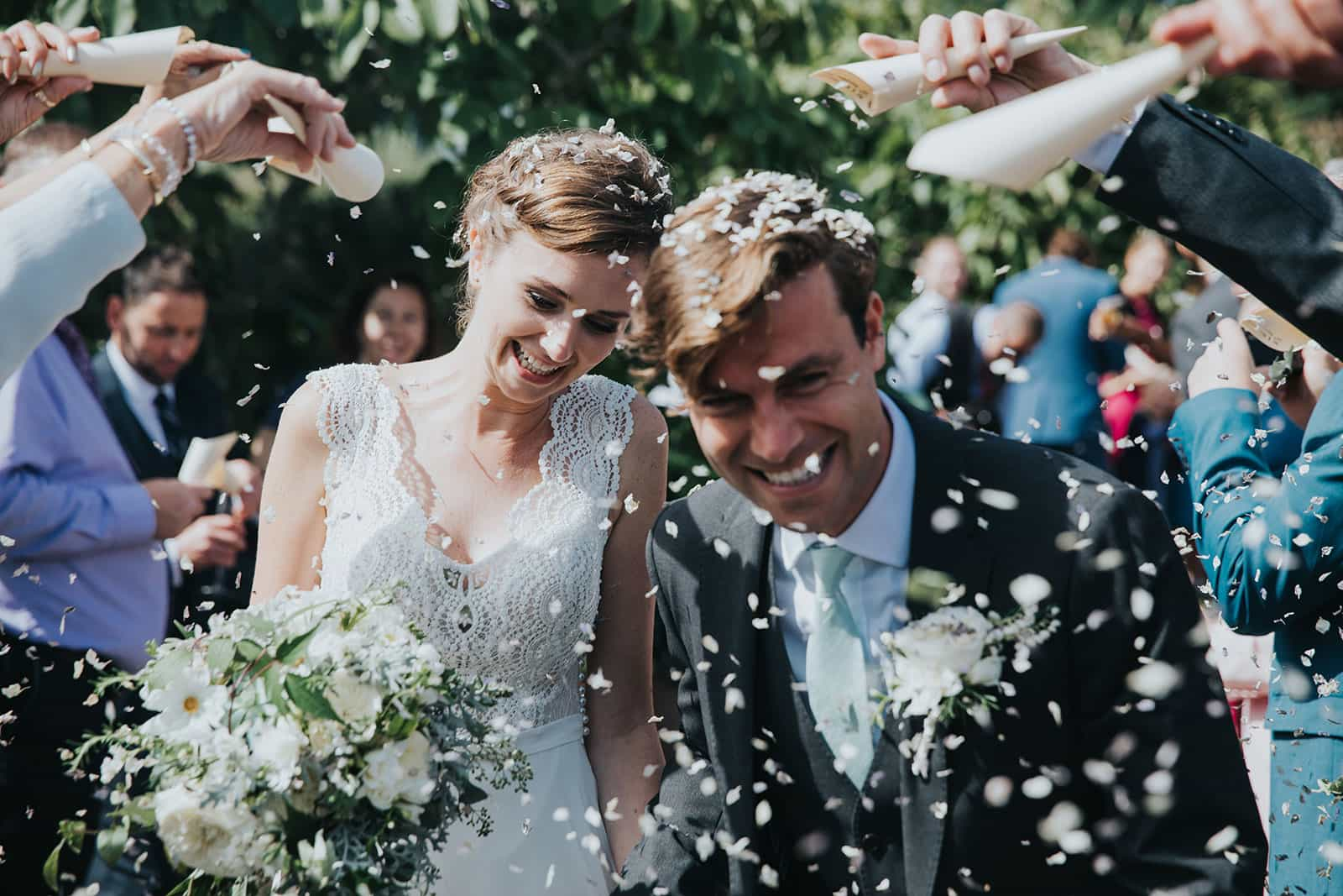 A photograph of newly weds and confetti being thrown at their tropical garden wedding