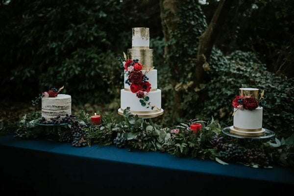 three different size wedding cakes on a decorative table with flowers