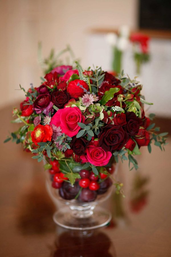 A photograph of the stunning red wedding flowers by Jenny Rose flowers, in Conrwall, as featured on eeek! weddings