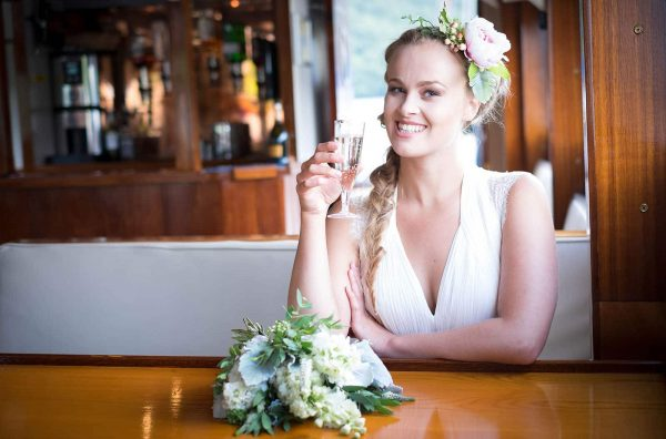 Bride drinking champagne on a boat by Verity Westcott Photography