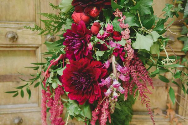 A photograph of a beautiful red flower arrangement at a private garden wedding