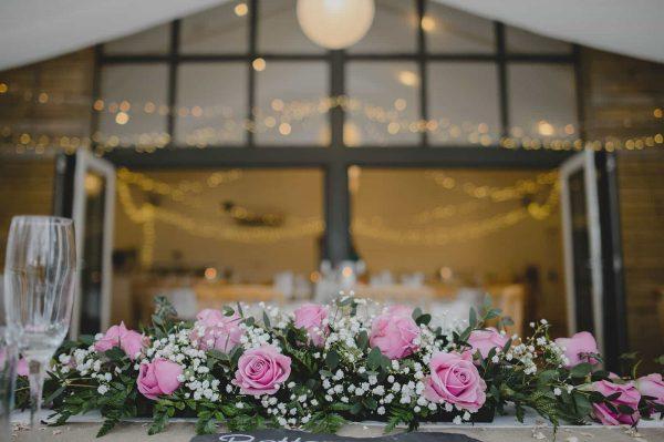 A photograph of beautiful blush pink roses at a barn wedding