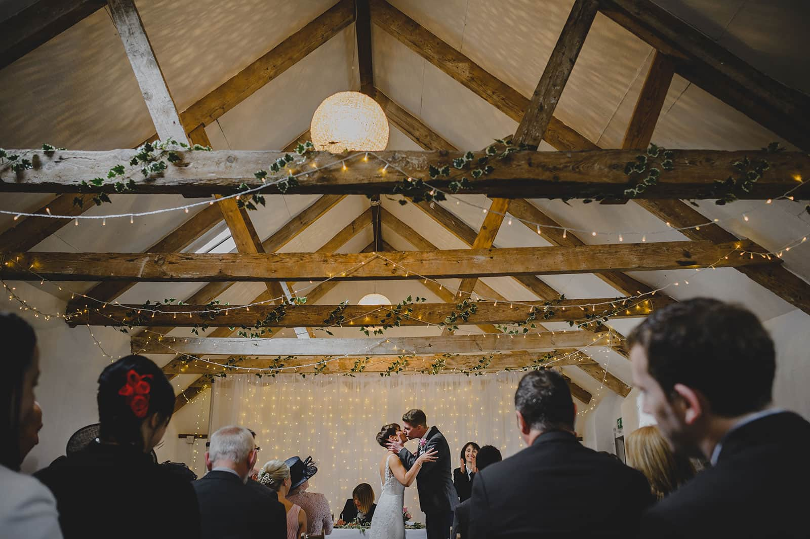 Newly weds kissing after the ceremony in a wedding barn at a A Countryside wedding venue