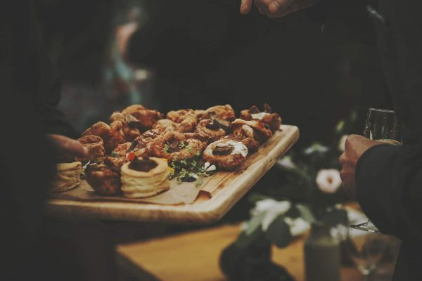 Delicious canapes being served on a wooden platter by Kerra's Catering as featured on eeek! weddings
