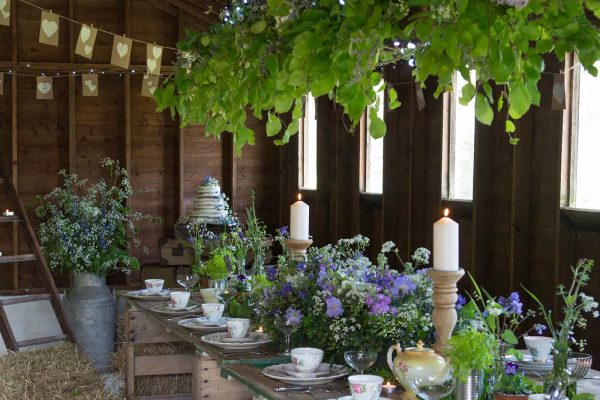 A rustic barn wedding reception with vintage crockery, flowers and candles