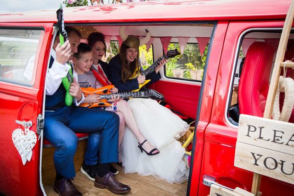 Wedding guests getting their photo taken in a VW Camper photobooth