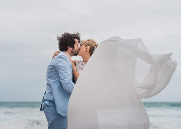 Bride and groom kissing on a beach, wedding dress being blown by the wind by John Barwood Photography