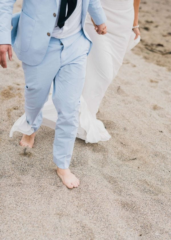 A photograph of bride and groom with sand between their toes at their relaxed beach wedding