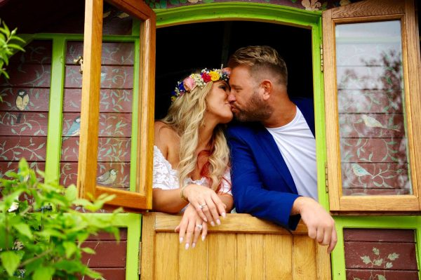 Newly weds kissing standing in a colourful gypsy caravan at Lower Barns Wedding Venue as featured on eeek! weddings