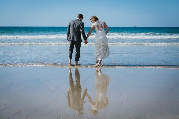 A photograph of a bride and groom on beach, Lusty Glaze Beach Weddings