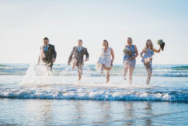 Wedding party splashing around in the sea at a Lusty Glaze Beach Wedding.