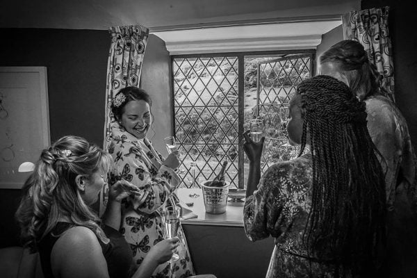 bride and bridesmaids laughing by Nick Pearce Photography