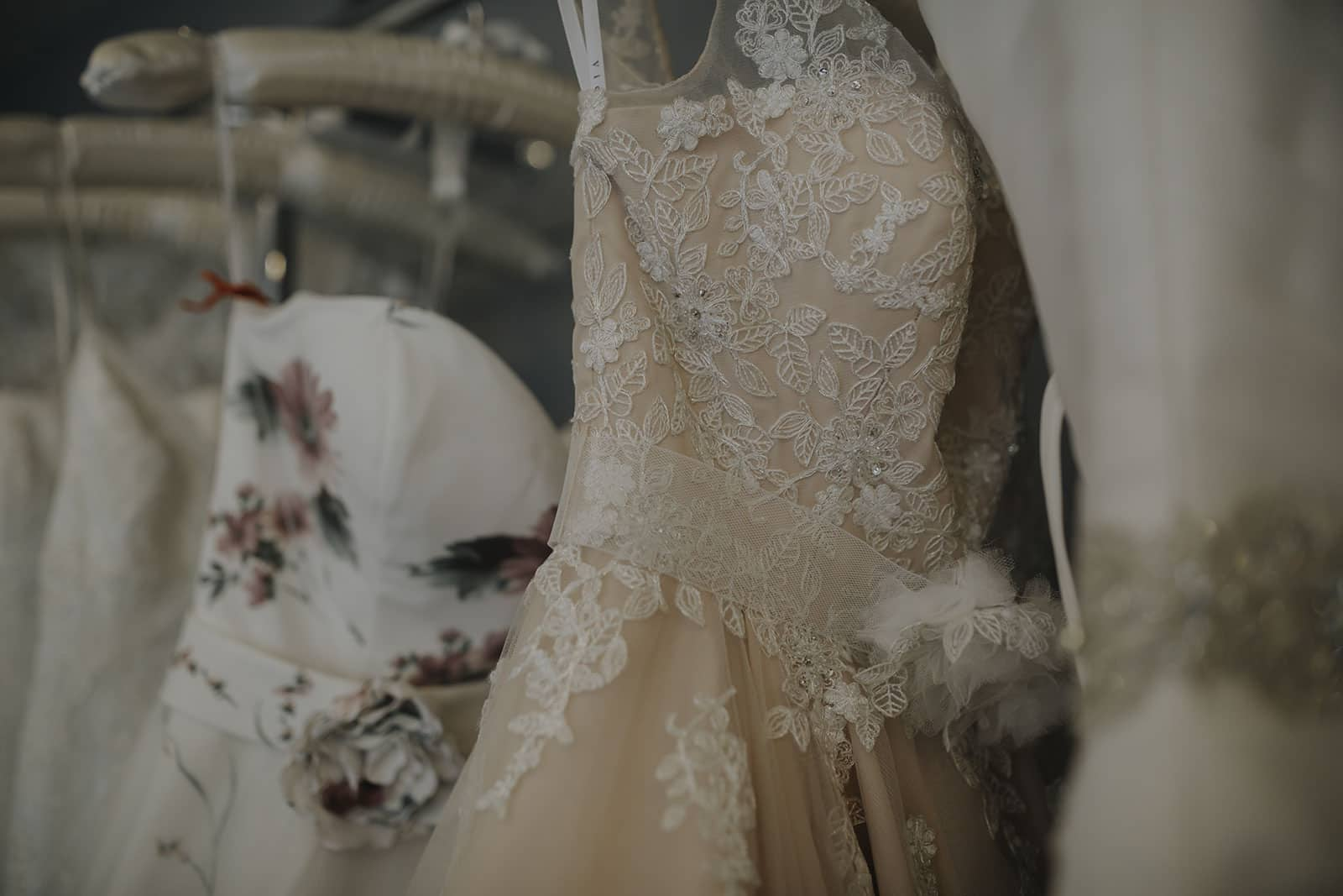 A photograph of beautiful wedding gowns hanging in a row at a bridal studio
