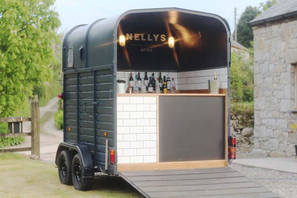 A photograph of a horse box that has been converted into a quirky mobile bar