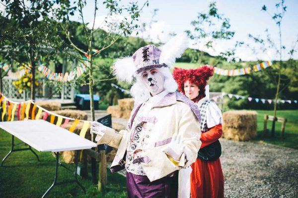 A photograph of The White Rabbit and the Queen of Hearts at a Mad Hatters Tea Party Wedding Reception