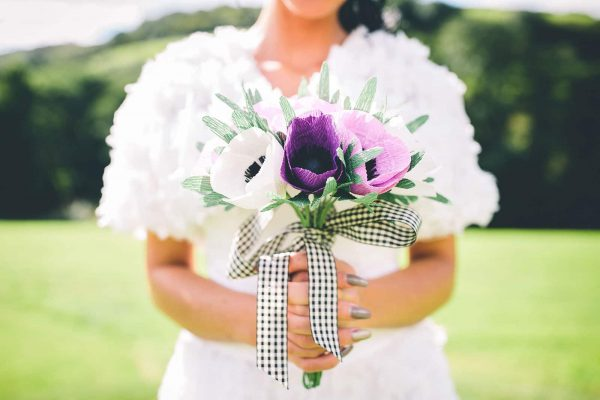 A bride holding beautiful handmade paper wedding flowers