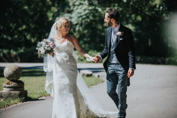 A photograph of newly weds walking hand in hand an English Country Garden Wedding
