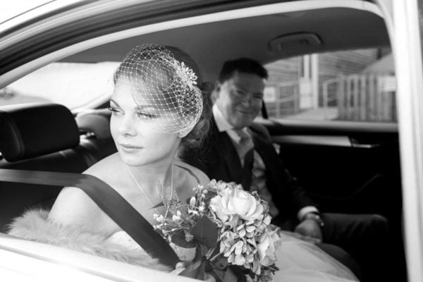 A photograph of a bride looking out of the car window on her way to get married, natural reportage style of photography