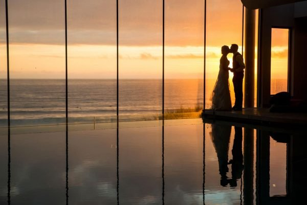 A photograph of a couple kissing by an infinity pool looking out to sea with a beautiful sunset. Style of photography natural reportage