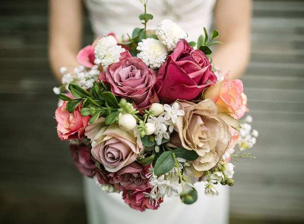 A photograph of a bride holding a bouquet of beautiful silk flowers