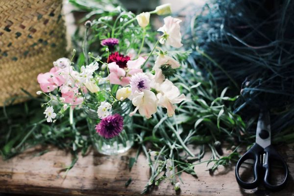A Photograph of beautiful home grown wedding flowers in a jam jar