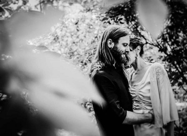 Newly engaged couple cuddling in a garden by Verity Westcott Wedding Photographer
