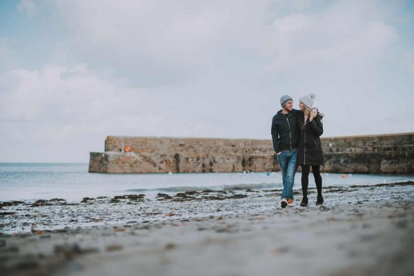 newly engaged couple walking along a beach