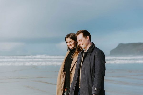 Alex and Piran's Engagement shoot with Wild Tide Weddings the couple are walking on a beach