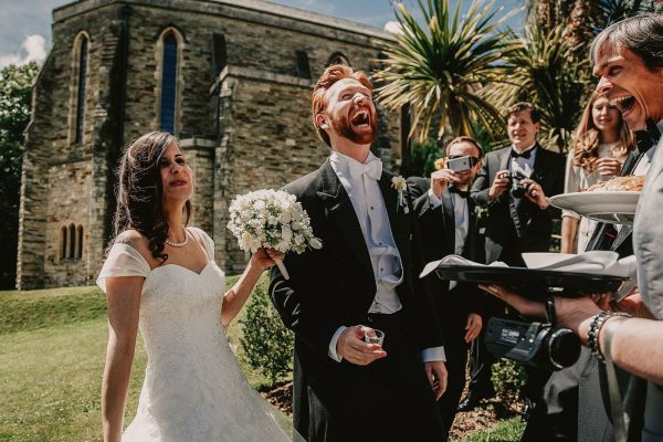Newly weds laughing outside of church captured by Andrew George Wedding Photography
